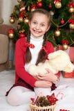 Flickan sitter nära julgranträd och att spela med björnen, hemmastadd julgarnering, lycklig sinnesrörelse, begrepp för vinterferi royaltyfria foton