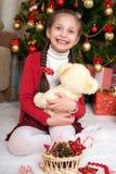 Flickan sitter nära julgranträd och att spela med björnen, hemmastadd julgarnering, lycklig sinnesrörelse, begrepp för vinterferi Arkivfoto