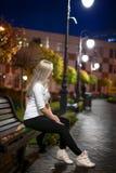 Flickan sitter på bänken i parkera - natt Arkivbild