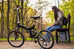 Flickan sitter p? b?nken, och det finns en cykel framme av henne arkivbilder