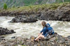 Flickan sitter på banken av en bergflod Royaltyfri Bild