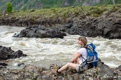 Flickan sitter på banken av en bergflod Royaltyfria Bilder