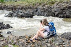 Flickan sitter på banken av en bergflod Fotografering för Bildbyråer