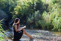 Flickan sitter på bankerna av floden och läser boken arkivbild