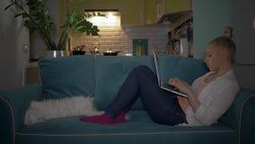 Flickan sitter på datoren och arbetar på en bärbar dator Flicka som sitter på soffan med katten och arbetar på datoren lager videofilmer