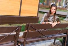 Flickan sitter på en bänk Royaltyfri Foto