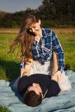 Flickan sitter på en grabb på picknicken Arkivbilder