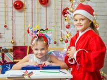Flickan sitter på en tabell med fyrverkerier på huvudet med en gåva som framläggas för att avla Christmas Royaltyfria Foton