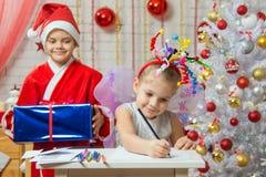 Flickan sitter på en tabell med fyrverkerier på huvudet, Santa Claus förbereder sig att förvåna henne Arkivbild