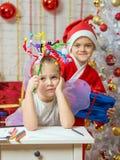 Flickan sitter på en tabell med fyrverkerier på huvudet, Santa Claus hennes klart att ge henne en gåva Royaltyfri Foto