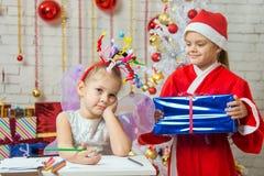 Flickan sitter på en tabell med fyrverkerier på huvudet, Santa Claus kommer med henne en gåva Arkivbild