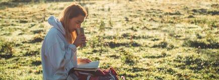 Flickan sitter på en träbänk i bergen i natur, läser en bok, dricker varmt te från en thermo kopp Begrepp som läser i natur fotografering för bildbyråer