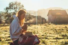 Flickan sitter på en träbänk i bergen i natur, läser en bok, dricker varmt te från en thermo kopp Begrepp som läser i natur arkivfoton