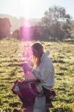 Flickan sitter på en träbänk i bergen i natur, läser en bok, dricker varmt te från en thermo kopp Begrepp som läser i natur royaltyfria foton