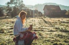 Flickan sitter på en träbänk i bergen i natur, läser en bok, dricker varmt te från en thermo kopp Begrepp som läser i natur arkivfoto
