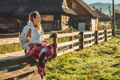 Flickan sitter på en träbänk i bergen i natur, läser en bok, dricker varmt te från en thermo kopp Begrepp som läser i natur arkivbilder