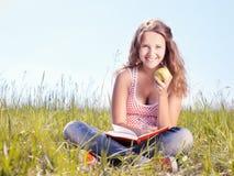 Flicka med ett äpple fotografering för bildbyråer