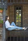 Flickan sitter på farstubron av ett trähus arkivfoto