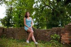 Flickan sitter på gamla förstörda väggar av slotten Royaltyfria Bilder