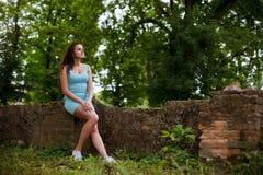 Flickan sitter på gamla förstörda väggar av slotten och ser t Royaltyfri Bild