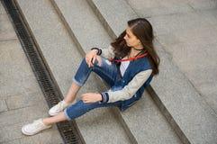 Flickan sitter på gatan på trappan Arkivbild
