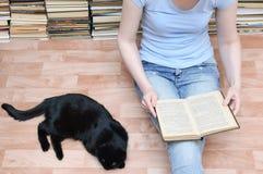Flickan sitter på golvet och läser en bok bredvid ligga för svart katt Närbild royaltyfri fotografi