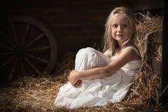 Flickan sitter på hö i ladugården Arkivbilder