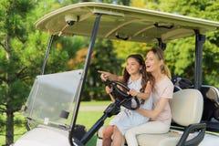 Flickan sitter på hennes varv nära en kvinna som kör en golfvagn Flickan pekar riktningen till var att gå royaltyfria bilder