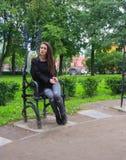 Flickan sitter på järnbiskopsstolen Arkivbild