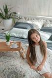 Flickan sitter på kanten av den vita sängen i ett ljust rum Arkivbild