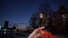 Flickan sitter på natten i staden