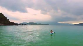 Flickan sitter på paddleboardsegling för att öppna havet på soluppgång stock video