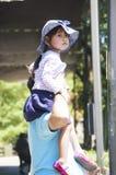 Flickan sitter på pappans skuldra Arkivfoton