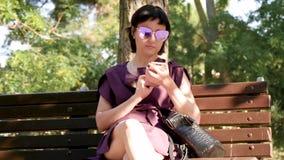 Flickan sitter på parkerar bänken och använder en smartphone för att meddela på sociala nätverk Ung brunettkvinna in stock video