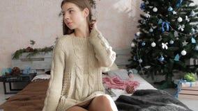 Flickan sitter på sängen bredvid julgranen Atmosfär för ` s för nytt år stock video