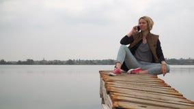 Flickan sitter på skeppsdockan som talar på telefonen stock video
