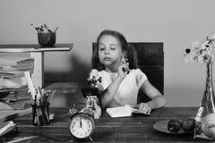 Flickan sitter på skrivbordet med böcker och klockan Skolflickan med den intresserade framsidan skriver i förskriftsbok Royaltyfria Bilder