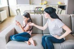 Flickan sitter på soffa- och innehavtelefonen i händer Hennes mamma argumenterar med barnet Hon pekar på telefonen Flickan är upp arkivfoton