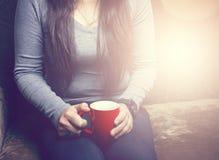 Flickan sitter på soffan och dricka Fotografering för Bildbyråer