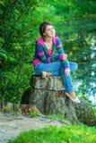Flickan sitter på stump Arkivfoton