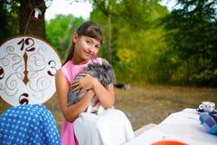 Flickan sitter på tabellen och innehavet en kanin Alice in Royaltyfri Foto