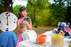 Flickan sitter på tabellen och innehavet en kanin Alice in Royaltyfria Foton