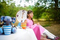 Flickan sitter på tabellen och innehavet per kopp te _ Arkivfoto