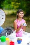 Flickan sitter på tabellen och innehavet per kopp te _ Royaltyfri Foto