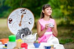Flickan sitter på tabellen och innehavet per kopp te _ Arkivfoton