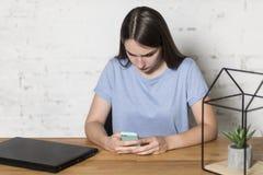 Flickan sitter på tabellen och rymmer telefonen i hennes händer Hon skriver meddelanden Det finns en bärbar dator på tabellen arkivbilder