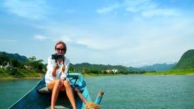 Flickan sitter på träfartygpilbåge gör selfie mot floden arkivfilmer
