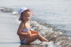 Flickan sitter på vattnets kant Arkivfoton
