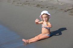 Flickan sitter på vattnets kant Arkivbilder