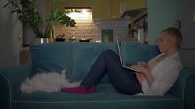 Flickan sitter p? datoren och arbetar p? en b?rbar dator Flicka som sitter p? soffan med katten och arbetar p? datoren lager videofilmer